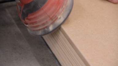 A sander is used to round over an MDF edge.