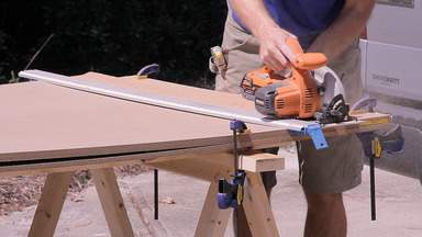 A circular saw is used to cut two pieces of MDF at once.