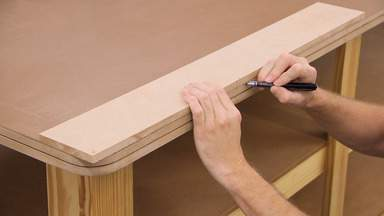 A pencil is used to transfer marks from a piece of MDF to a workbench top.