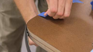 Blue painters tape is used to secure the T-molding onto the edge of the workbench top.