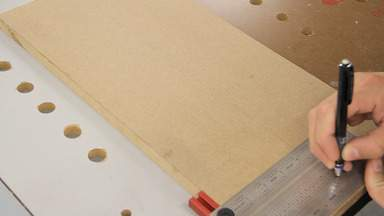 A pencil and square are used to mark a line down a piece of MDF.