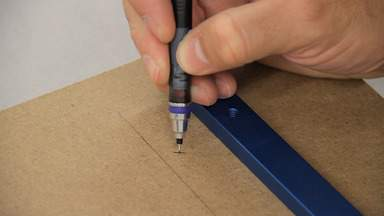 A pencil is used to mark hole locations on MDF.